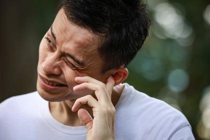 耳に痛みを感じる男性