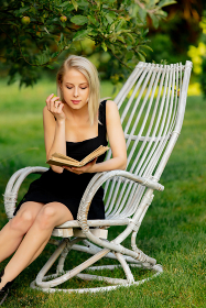 Blonde woman sitting in wooden armchair with book in an apple tr , Wrocław, Lower Silesian Voivodeship, Poland