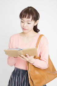 スケジュール帳を見る女性の手元