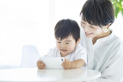 スマートフォンの画面を見る子供とお母さん