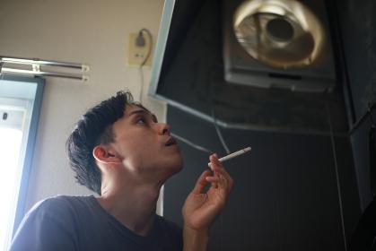 換気扇の下でタバコを吸う男性