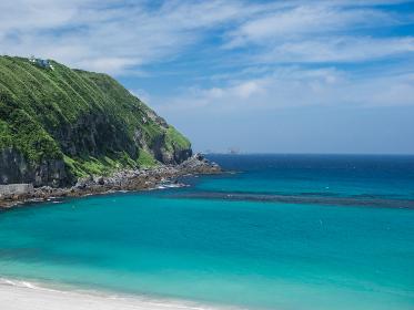 真夏の神津島の風景 エメラルドグリーンの海と白い砂浜の前浜海岸と水平線 8月