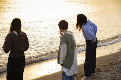 夕暮れの中、海沿いで遊ぶ若い女性4人