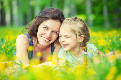 Mother and daughter on sunny meadow