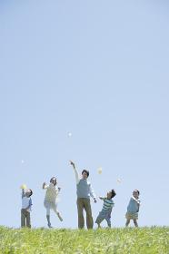 草原で紙飛行機を飛ばす小学生と先生