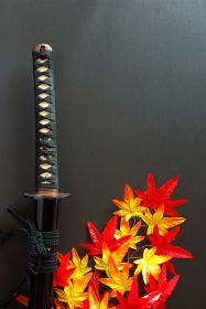 納刀した居合練習刀と造花の紅葉