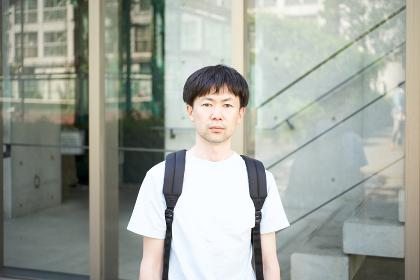 建物の前に立つ真剣な表情の男性