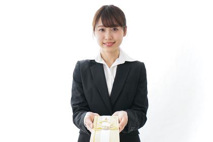 祝儀袋を渡すスーツ姿の女性