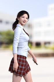 スマートフォンを片手に持った笑顔の一つくくりの女子高生が校舎へと移動している