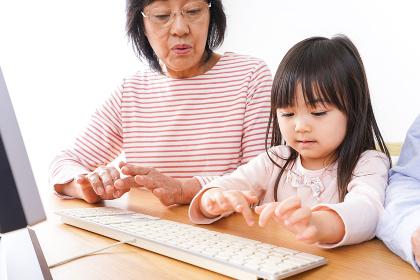 パソコンを使う祖父母と子ども