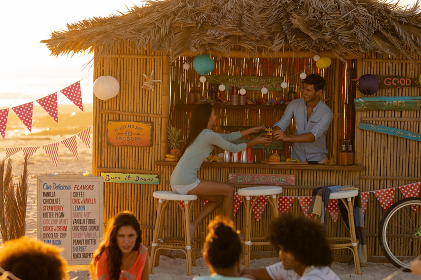 Mixed race woman and Caucasian man enjoying their time on a beach with their freinds during a sunset, sitting by a surfing lessons hut, talking