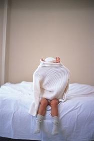 ベッドの上で大きな服を着る子ども