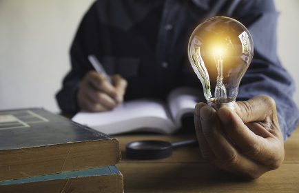 Hand of male holding a light bulb with pile of books for education and creative concept.