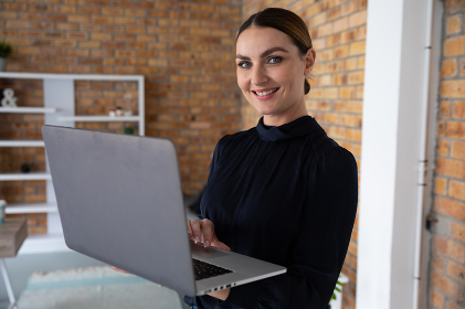 Portrait of Caucasian professional woman with long dark hair in a bun wearing smart casual blouse in office, using her laptop. Hygiene in the workplace during Coronavirus Covid 19 pandemic.