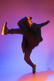 The silhouette of one hip hop male break dancer dancing on colorful background