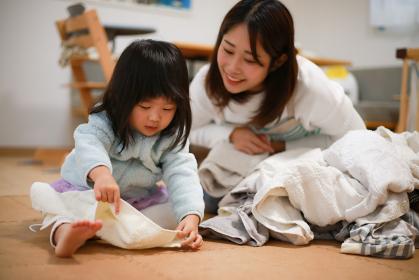 洗濯物をたたむ手伝いをする女の子