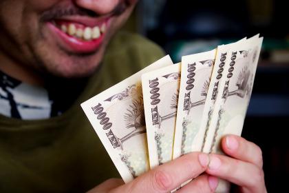 お金を見て笑う男性