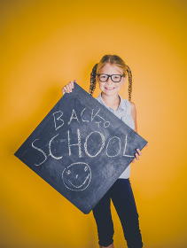 beautiful blond girl with glasses holding blackboard with the words back to school in front of orange background