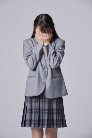 顔を手で覆う女子中学生
