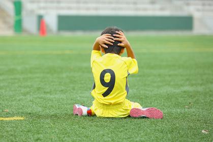 がっかりするサッカー少年