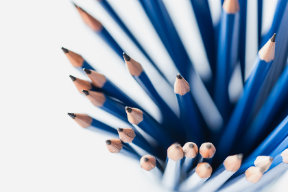Overhead view of bunch of sharpened blue pencils on white paper.