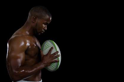Side view of shirtless male athlete holding rugby ball