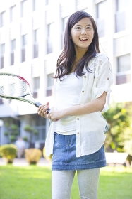 テニスラケットを持って微笑む女子大学生