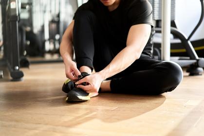 トレーニングジムで靴紐を結びアジア人男性
