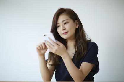 携帯電話を操作する日本人女性のポートレート