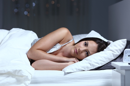 Serious woman looking at camera in the night in the bed