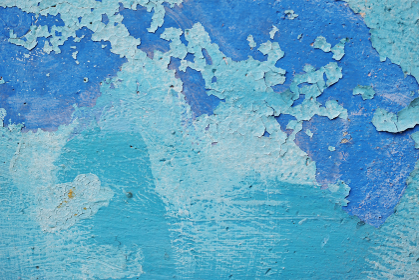 くすんだ青色と水色のペンキが塗られた古いコンクリートの壁