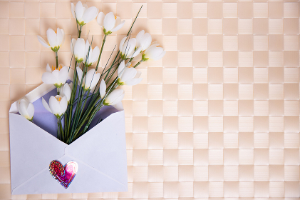 Happy Valentine or Mothers Day background. Beautiful bouquet of white flowers in an open envelope with a hearts symbol lying on a bright table. Space for your design on the right side.