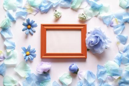 白背景に青色の造花と花びら。中央に横長の木製フォトフレームと白いコピースペース。平置きの俯瞰撮影。