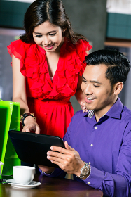Young couple watching a funny video on a tablet connected to the internet