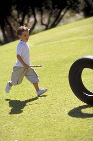 Parkszene, Portrait, Ganzfigur, 6-jaehriger Junge, bekleidet mit weissem T-Shirt, halblanger Hose und weissen Turnschuhen spielt im Spaetsommer auf einer Wiese mit einem Autoreifen