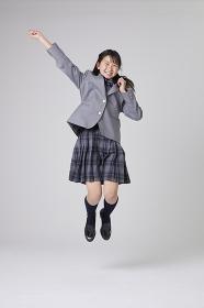 腕を伸ばしジャンプする女子中学生