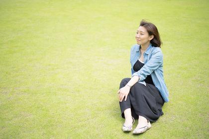 爽やかな草原に座る1人の女性