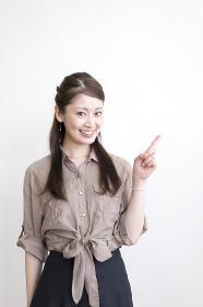 女性・指差し(笑顔)