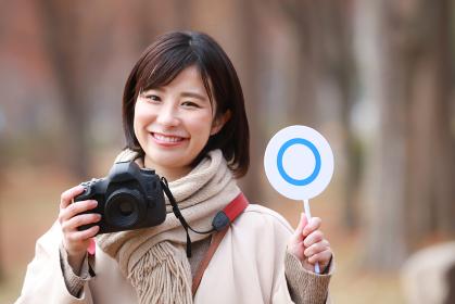 一眼レフカメラと〇札を持つ女性
