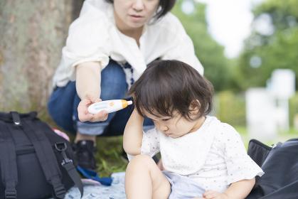 屋外で、非接触型の機器で子供の体温を測る母親