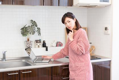 キッチンでパソコンを見る女性 考える