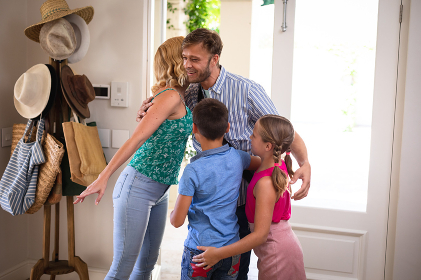 Happy caucasian couple with son and daughter at home, smiling and embracing. family enjoying quality free time together.