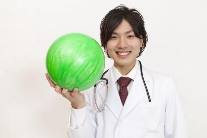 ボウリング球を持って微笑む医師