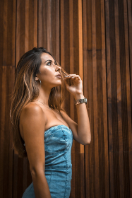 Young woman on a wooden background in a blue dress looking at the sky