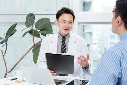患者の症状を聞く医者