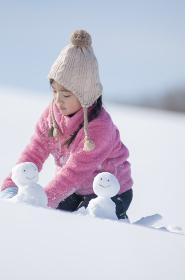 雪原で雪だるまを作る女の子