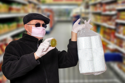 Coronavirus panic concept. Man with surgical mask, hood, glasses and medical gloves shows a package of toilet paper and an abstract model of a virus covid-19 over blurred super market background.