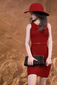 赤い帽子をかぶったセミロングの女性がノースリーブのタイトなワンピースを着て斜め後ろ下を見つめながら前方に進むポーズ