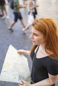 Portrait of a woman standing in the city holding a city map