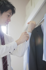 シャツのボタンを留める男性